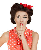 Pin-up style girl with finger on lips — Stock Photo
