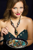Young woman holding fork and plate with jewelry — Stock Photo