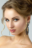 Beauty portrait of young woman with black earrings — Stock Photo