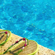 Two flip flops on the platform beside swimming pool — Stock Photo #44204251