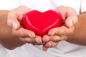 Male hands giving red heart — Stock Photo