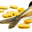 Fish oil capsules and fish tail in brown jar — Stock Photo #48360597