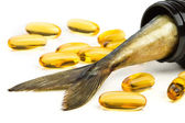 Fish oil capsules and fish tail in brown jar — Stock Photo