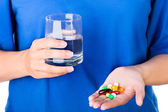 Woman holding glass of water and pack of pills — Stock Photo