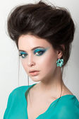 Beautiful young brunette woman in a turquoise dress — Stock Photo