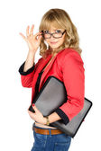 Blonde woman in red jacket with folder looking over her glasses  — Stock Photo