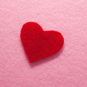 Felt red heart on pink background. — Stock Photo