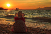 Denken vrouw zitten in de zonsondergang op het strand — Stockfoto