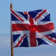 British Flag Union Jack blowing in the wind against a blue sky — Stock Photo #21816009