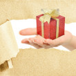 Hand break through paper with gift on hand — Stock Photo