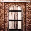 Wooden vintage closed door with brick wall — Stock Photo