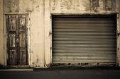 Porte d'obturateur de rouleaux métalliques grunge lumineux près de la porte en bois — Photo