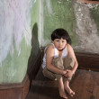 Frightened Boy in White Undershirt and Khaki Pants - Stock Photo