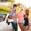 Three young friends travel by car - Stock Photo