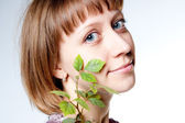 Young girl with a plant in the face — Stock Photo