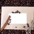 Coffee beans in a paper envelope with white card and a stick of cinnamon — Stock Photo