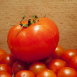 Big red tomato is on the small tomatoes — Stock Photo #26964641