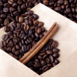 Coffee beans in a paper envelope with a stick of cinnamon — Stock Photo