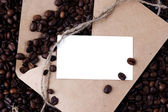 Coffee beans in a paper envelope with white card — Stock Photo