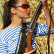 Young beautiful girl with a rifle hunts in the reeds. — Stock Photo