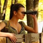 Armed young beautiful girl looking through binoculars — Stock Photo #41644087