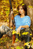 Girl sitting with a gun in his hand near a tree in the forest. — Stock Photo