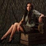 Girl uniform sitting on wooden crates. Camouflage. — Stock Photo