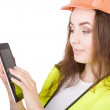 The girl the builder in a helmet and a vest with an electronic tablet in hands. It is isolated. white background. — Stock Photo #44154159