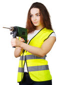 The girl in a construction vest with an electric drill in hands. — Stock Photo