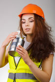 Girl in a helmet and vest looks into the open metal container. — Stock Photo