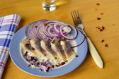 Portion herring fillet with onions and peppers on a wooden table — Stock Photo