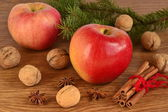 Red apple, walnuts, cinnamon and star anise on a wooden background — Stock Photo