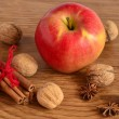 Red apple, walnuts, cinnamon and star anise on a wooden background — Stok fotoğraf