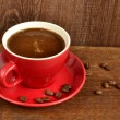 Red cup of coffee on old wooden table — Stock Photo #36540997