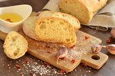 Fresh bread - ciabatta, chili and garlic on old wooden board — Stock Photo