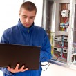 Electrician working with laptop — Stock Photo