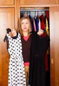 Undecided Woman with Dresses — Stock Photo