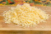 Grated cheese on a cutting board — Stock Photo