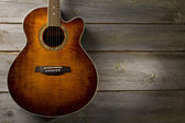 Acoustic guitar on wood background — Stock Photo