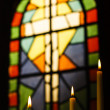Prayer Candles And Stained Glass Church Window - Stock Photo