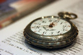 Old pocket watch lying on the book with the english text — Stockfoto