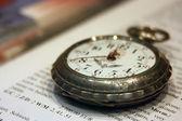 Vecchio orologio da tasca sdraiato sul libro con il testo inglese — Foto Stock