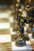 Antique chess pawns in the foreground — Stock Photo