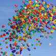 Many colored balloons flying in the blue sky — Stock Photo
