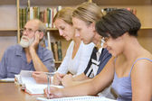 Multiracial group of four studying in library — Stock Photo