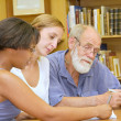 Old professor with multiracial group studying in library - Stock Photo