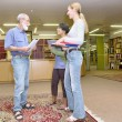 Multiracial group of friendly chatting in library - Stockfoto