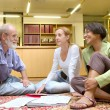 Stock Photo: Professor with students sit on carpet