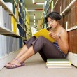 African girl reads book sitting on library floor — Stock Photo
