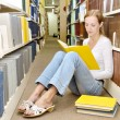 Slim girl sits on floor in library and reads book — Stock Photo #20253177